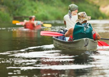 Four people canoeing and kayaking down the Au Sable River