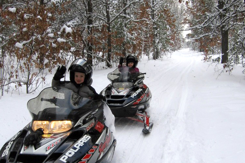 Kids snowmobiling along a groomed trail in Grayling, Michigan